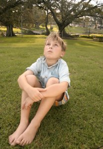 A boy sitting barefoot on the grass