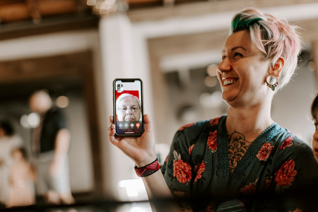 Woman holds up phone with mother on facetime chat