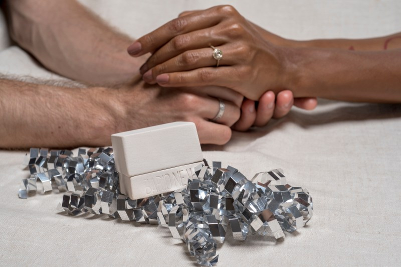 Photo of couple of hands embracing in the background with a porcelain ring box in the foreground