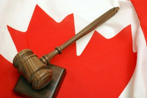 A gavel and sounding block rest atop a red maple leaf adorned to the flag of Canada.