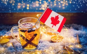 A cup of hot tea sits on a desk next to a window sill that is decorated in Christmas lights. On the table with the Christmas lights are cinnamon sticks, dried lemon slices and snow flakes. In the cup of tea are cinnamon sticks, anise cloves, slices of lemon, and one tiny Canadian flag sticking out of the side.