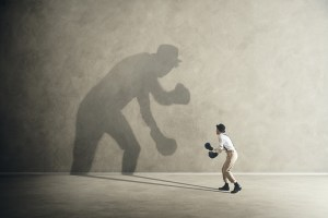 A man wearing boxing gloves attempts to fight his own shadow.
