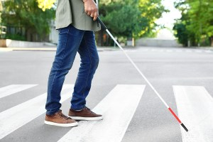 Close up waist down of a blind man with a white cane crossing the street.