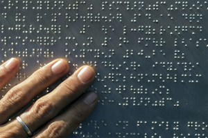 A male hand with a single sterling silver band on his middle finger places his hand on a metal plate with raised braille dots.