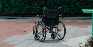 A wheelchair sits alone in a courtyard with a cane laid across the top of it.