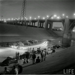 Drag racing and car exhibition on the Los Angeles Riverbed, under the classic Sixth Street Bridge. c. 1956