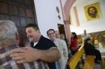 Francisco Gea Ramos saluda a un parroquiano, Rafael López, a la izquierda, después de un servicio en la iglesia del barrio.