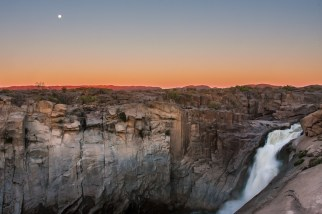 The moon rises as the sun disappears behind the horizon at The Augrabies Falls