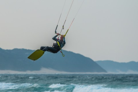 Kite surfer hangs in mid air with sea and sand dunes in the background