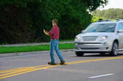 Man crossing in the street in front of a moving vehicle