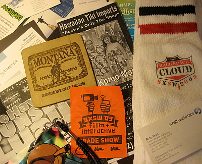 """Artefacts from the event: Rackspace tube socks, Montana film board leather coaster, business cards, BarCamp pass, brochure from """"Austin's only tiki shop"""" etc."""