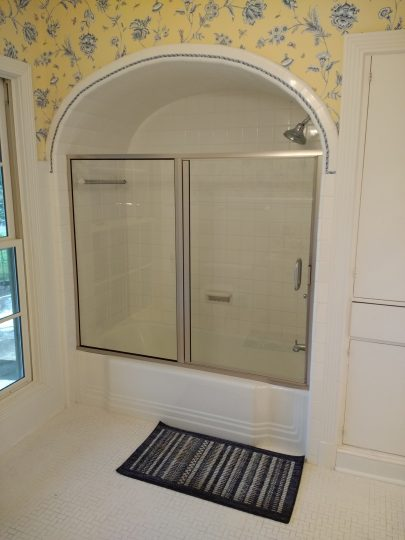 shower enclosure in arched opening over bathtub