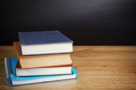 books on wooden deck table and grunge background