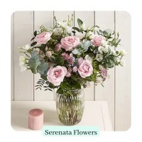 pink and white roses with olive branches in a glass vase