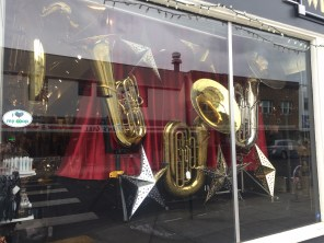 window display, tubas, red curtain background, Bellingham Wind Works