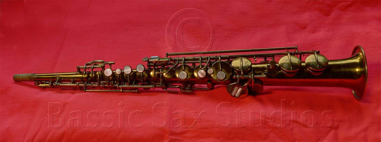 c pitched soprano sax, Conn New Wonder, gold lacquer sax on red background