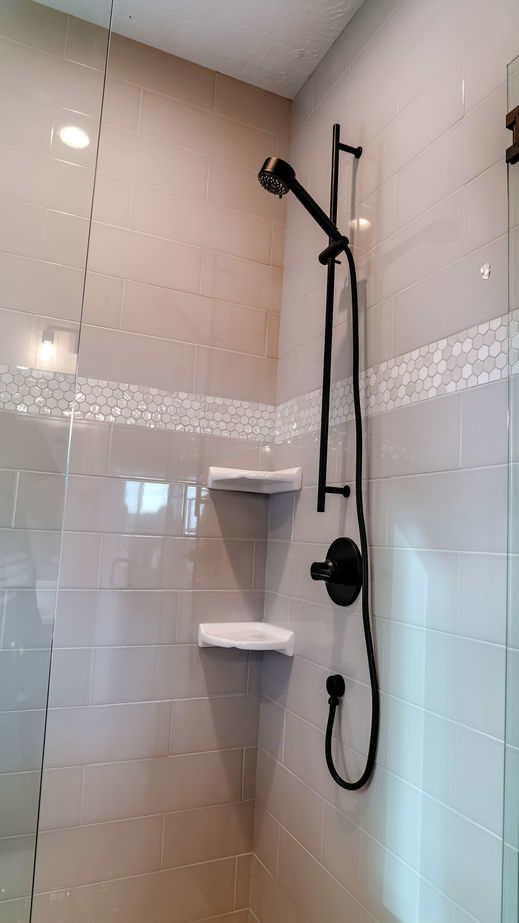 Vertical frame Black round shower head on tile wall of shower stall with hinged glass door