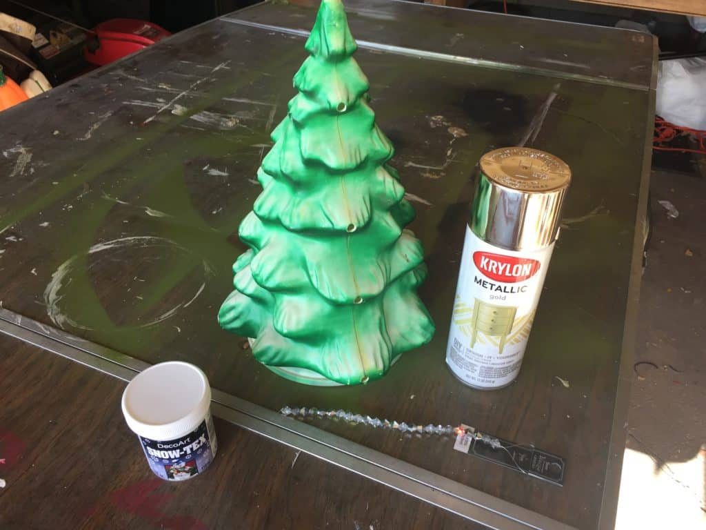 The supplies you will need: a plastic Xmas tree, spray paint, beads and lights