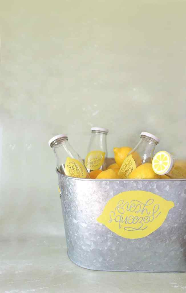 "A galvanized tub with a custom ""fresh squeezed lemonade"" sign"