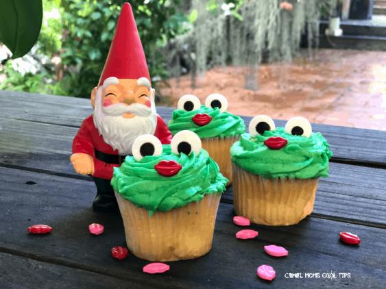 Three green frog cupcakes and a garden gnome.