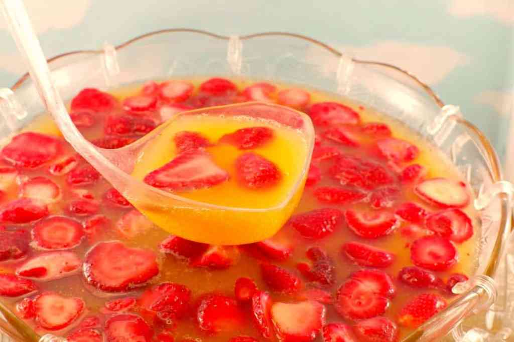 A glass fruit punch bowl filled with yellow punch and fresh strawberries.