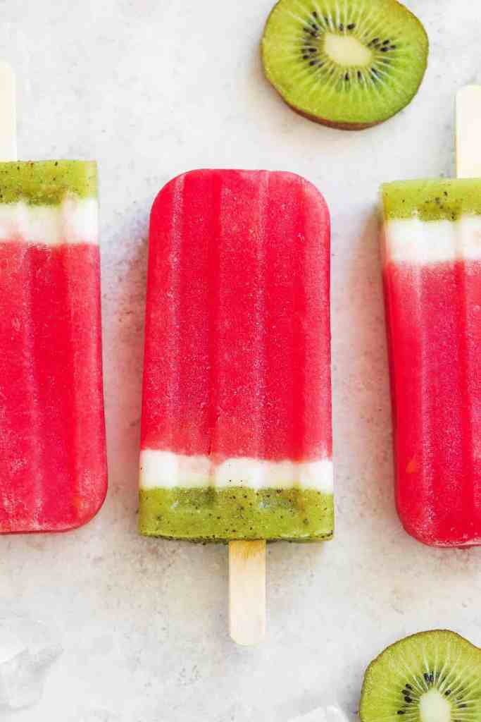 3 Red white and green layered strawberry Popsicles.