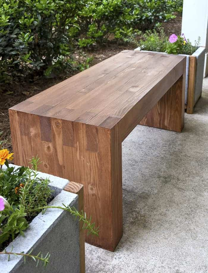 Create a modern backyard bench out of two by fours.