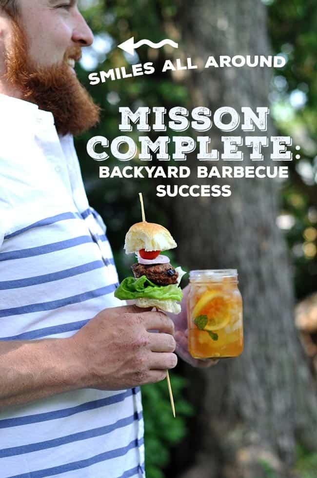 A man holding a hamburger on a stick and an iced tea.