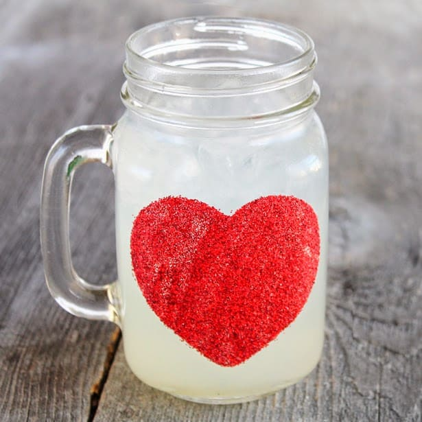 A mason jar mug with a glittery red heart.
