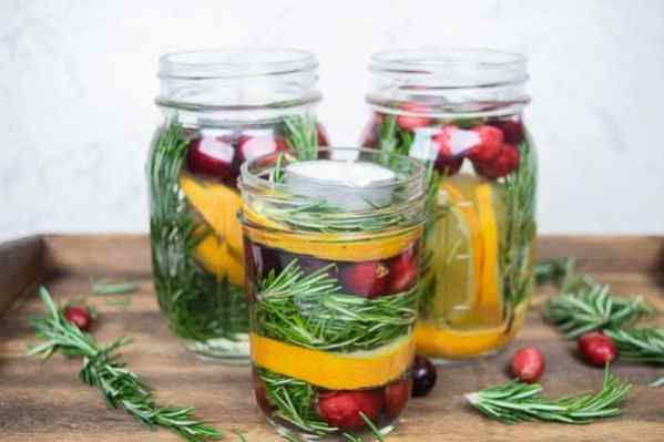 A mason jar centerpiece filled with Rosemary, oranges and cranberries.