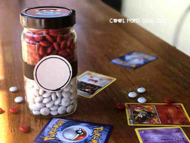 A Pokeball mason jar filled with white and red M&Ms.