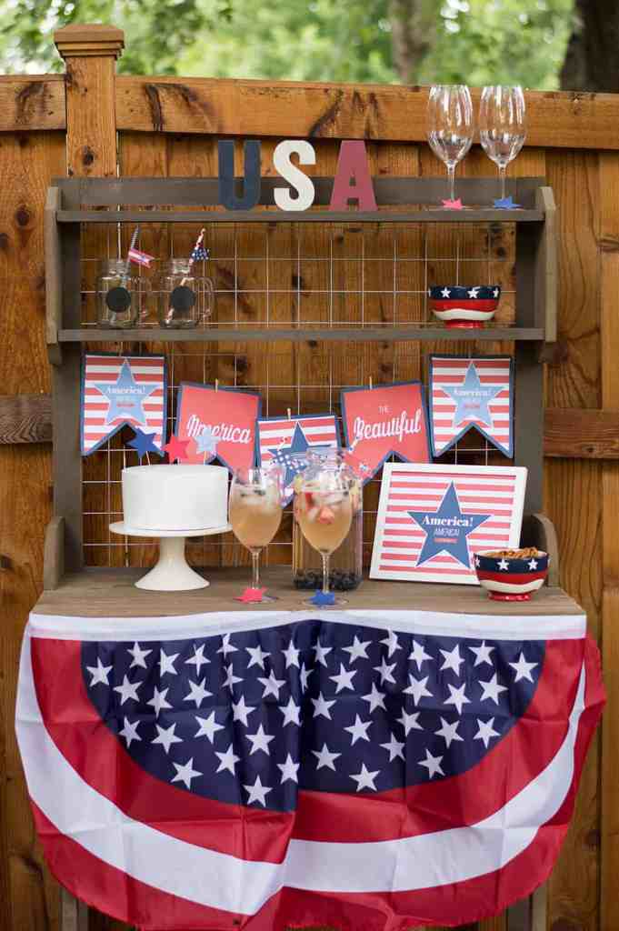 A table with 4th of July decorations and signs scattered over it.