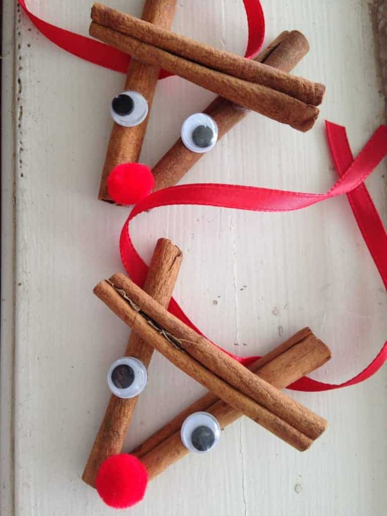Cinnamon sticks glued together to make a reindeer head with googly eyes and red ribbon