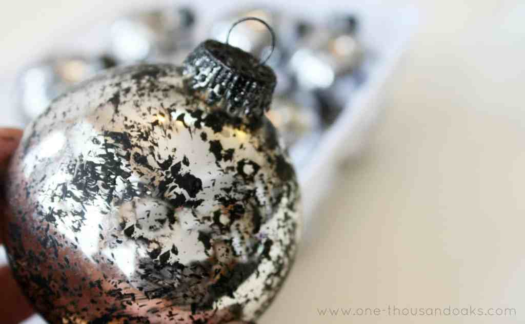 A silver ball ornament DIY with black paint dabs added,