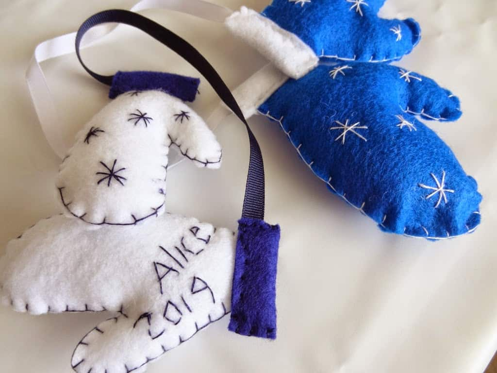 A blue and white felt mitten ornament with name and year added,