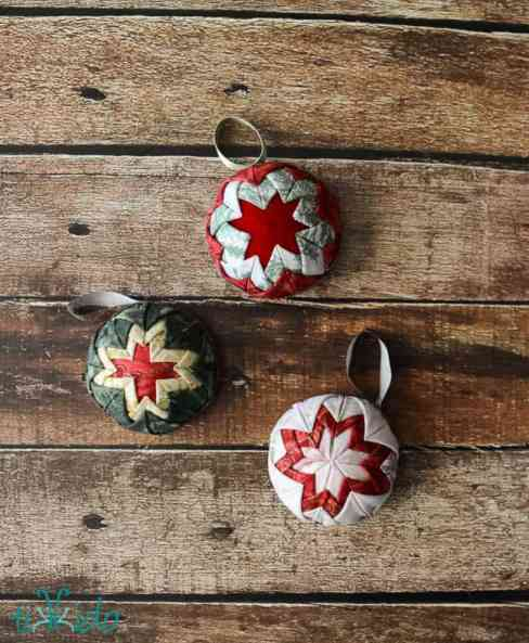 Three quilted Christmas tree ball ornaments in various colors with star patterns.