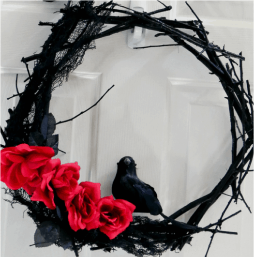 A black Halloween twig wreath with crows  and red roses