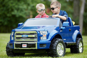 Boys wearing sunglasses riding in Power Wheels truck
