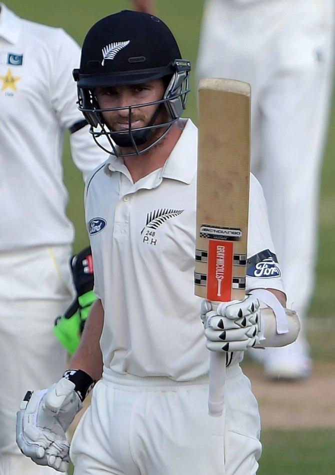 Williamson raises his bat after scoring his eighth Test century