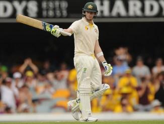 Smith raises his bat after scoring his half-century