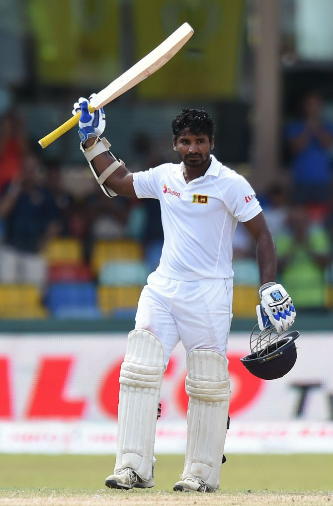 Perera raises his bat after scoring his maiden Test fifty
