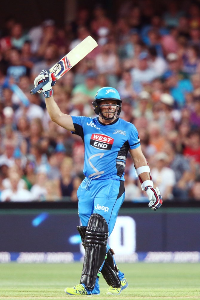 Hodge raises his bat after bringing up his half-century