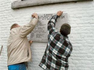 Securing the plaque to the memory of the British regiments that fought at Fontenoy to the church wall at Verzon