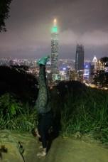 Handstand Steph on top of Elephant Mountain overlooking the Taipei skyline and 101 Taipei.