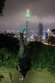 Handstand Steph on top of Elephant Mountain overlooking the Taipei skyline and 101 Taipei.