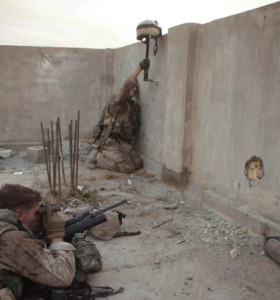 A Marine uses a breaching tool to prop up his helmet up above a wall in order to draw insurgent fire so that a rifleman can identify these targets and eliminate them during a security and stabilization operation conducted Nov. 9, 2004, as part of Operation Al Fajr. (Marine Corps)