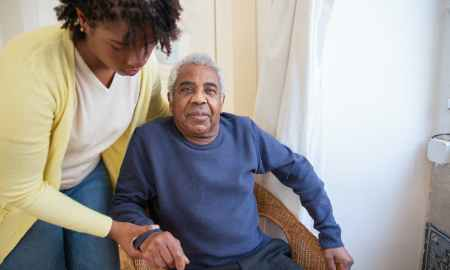 Black woman assisting elderly black man