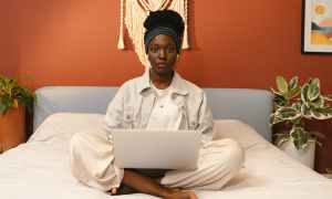 Black woman sitting on bed with laptop