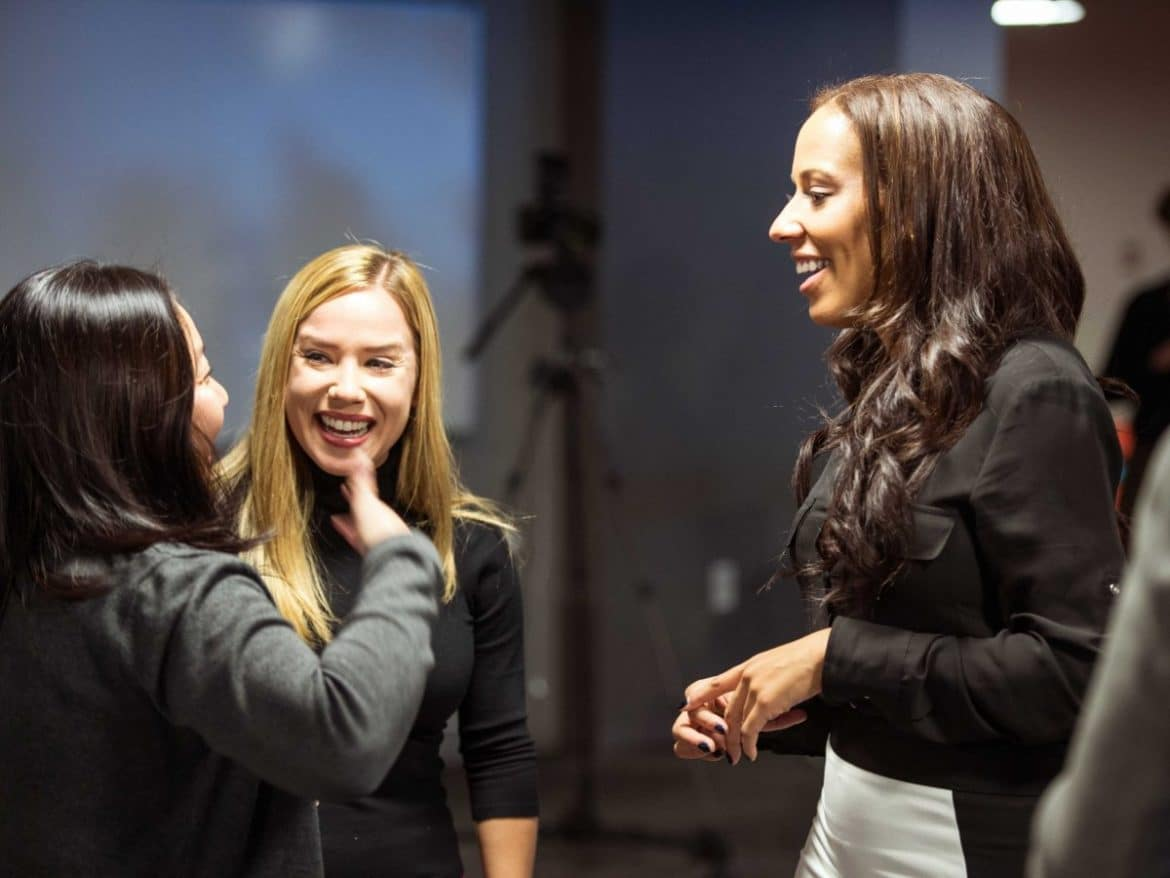 Three women standing, talking and laughing at networking event.