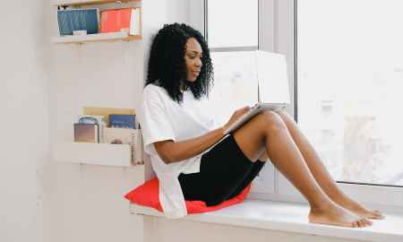 Black woman resting on window sill while using laptop